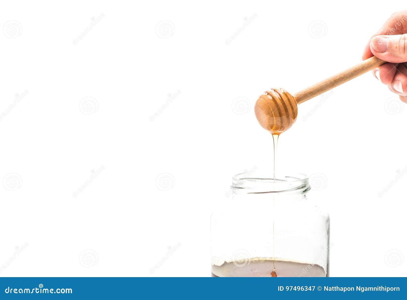 Gocciolamento del miele in barattolo