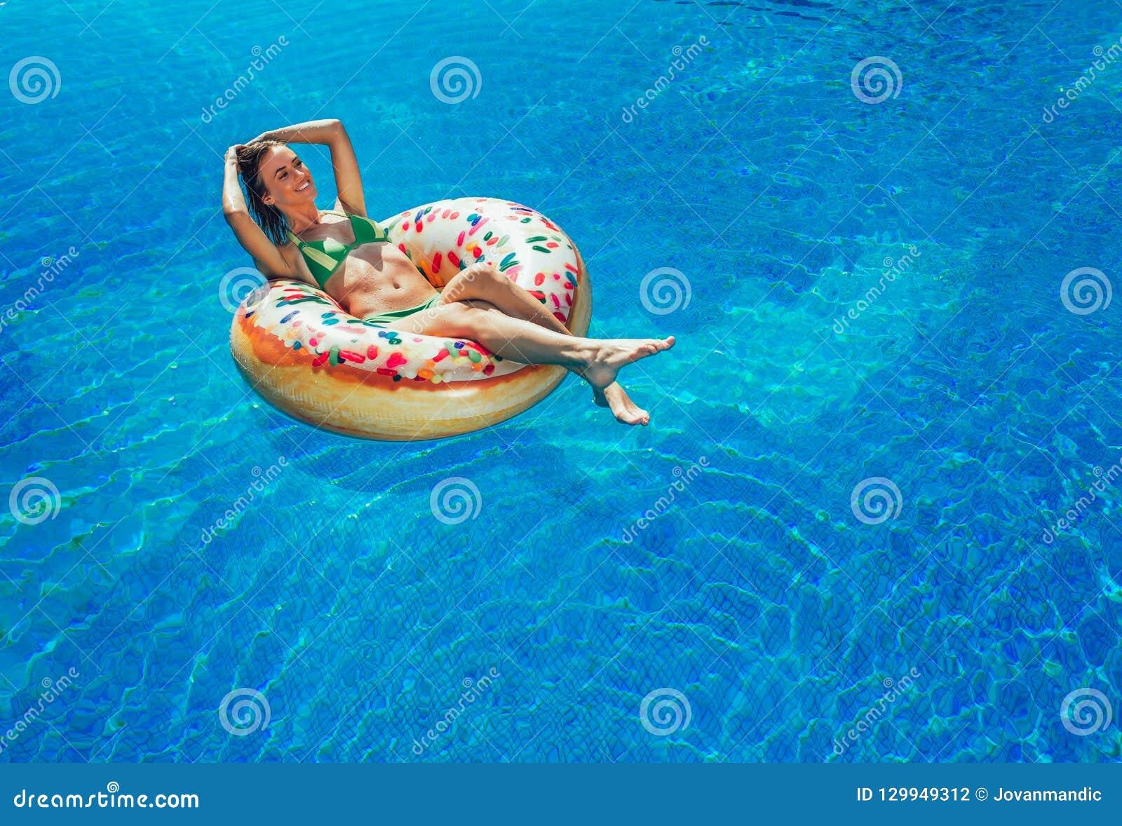 Goce de la mujer del bronceado en bikini en el colchón inflable