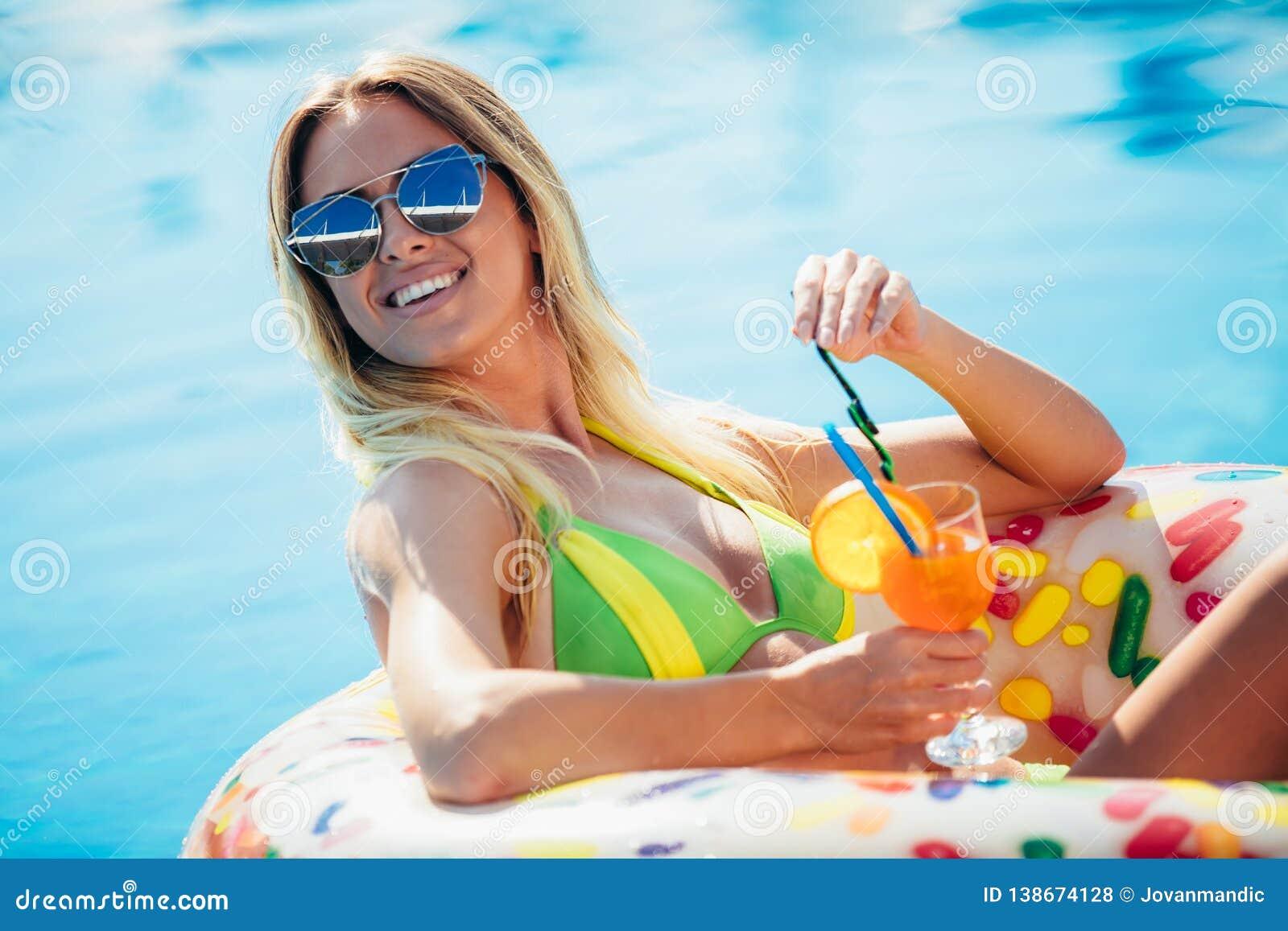 Goce de la mujer del bronceado en bikini en el colchón inflable en la piscina