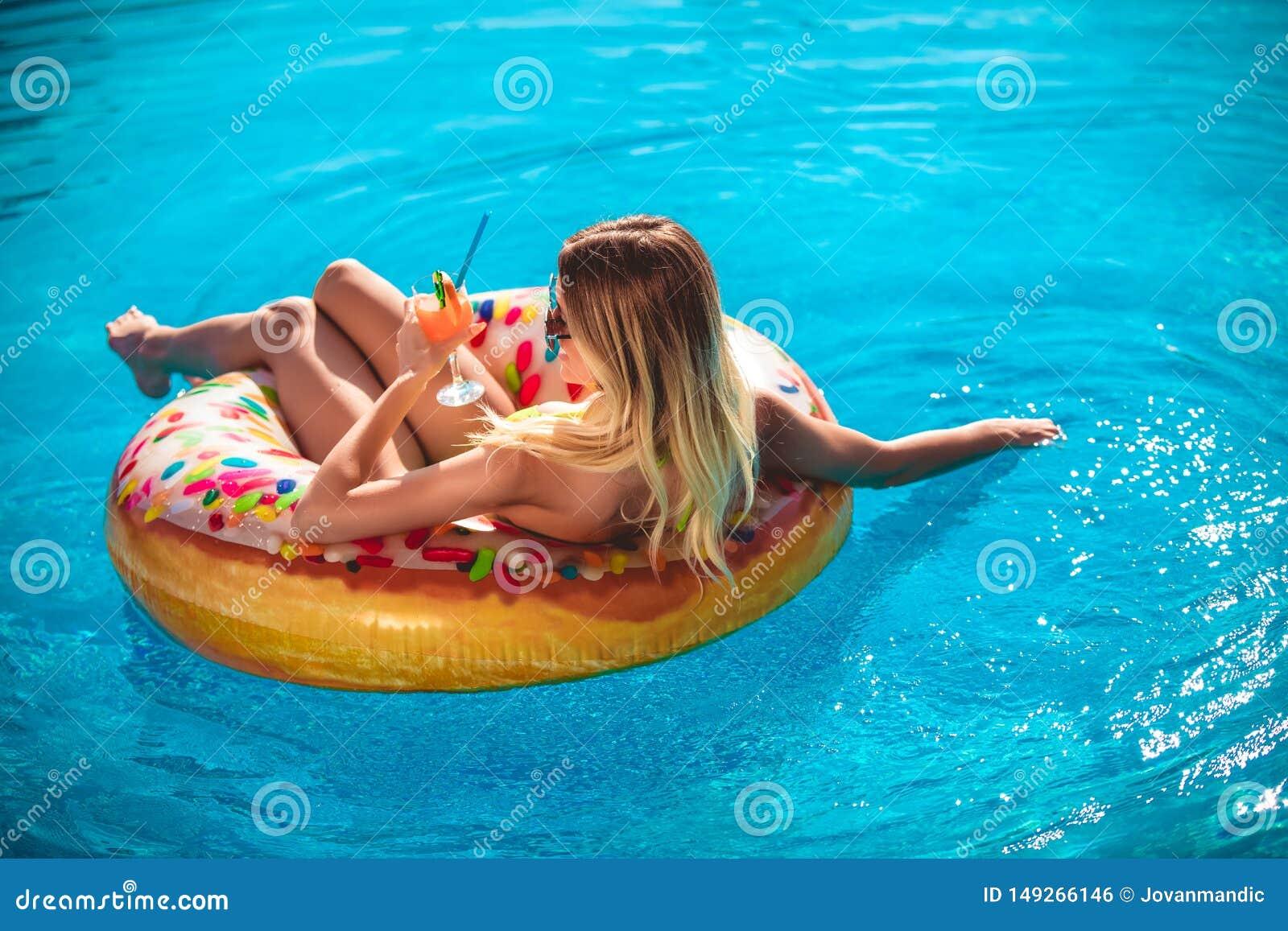 Goce de la mujer del bronceado en bikini en el colch?n inflable en la piscina