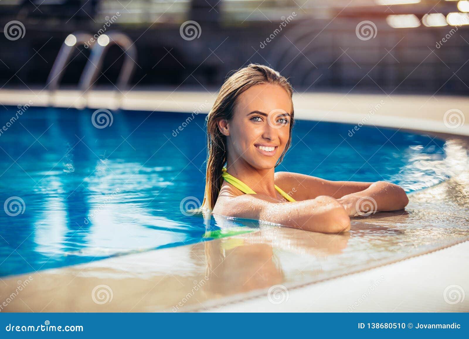 Goce de la mujer del bronceado en bikini en la piscina