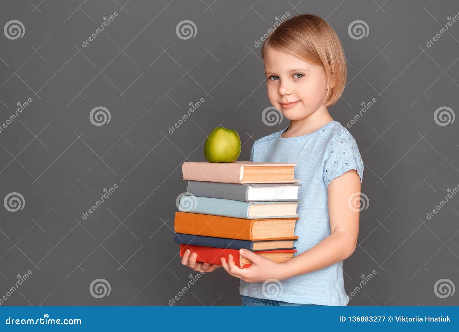 God deltagare Liten flicka som isoleras på grå färger med högen av böcker och att le för äpple som är blygsamt