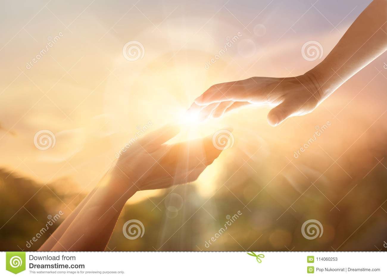 God`s helping hand with the white cross on sunset background. Da