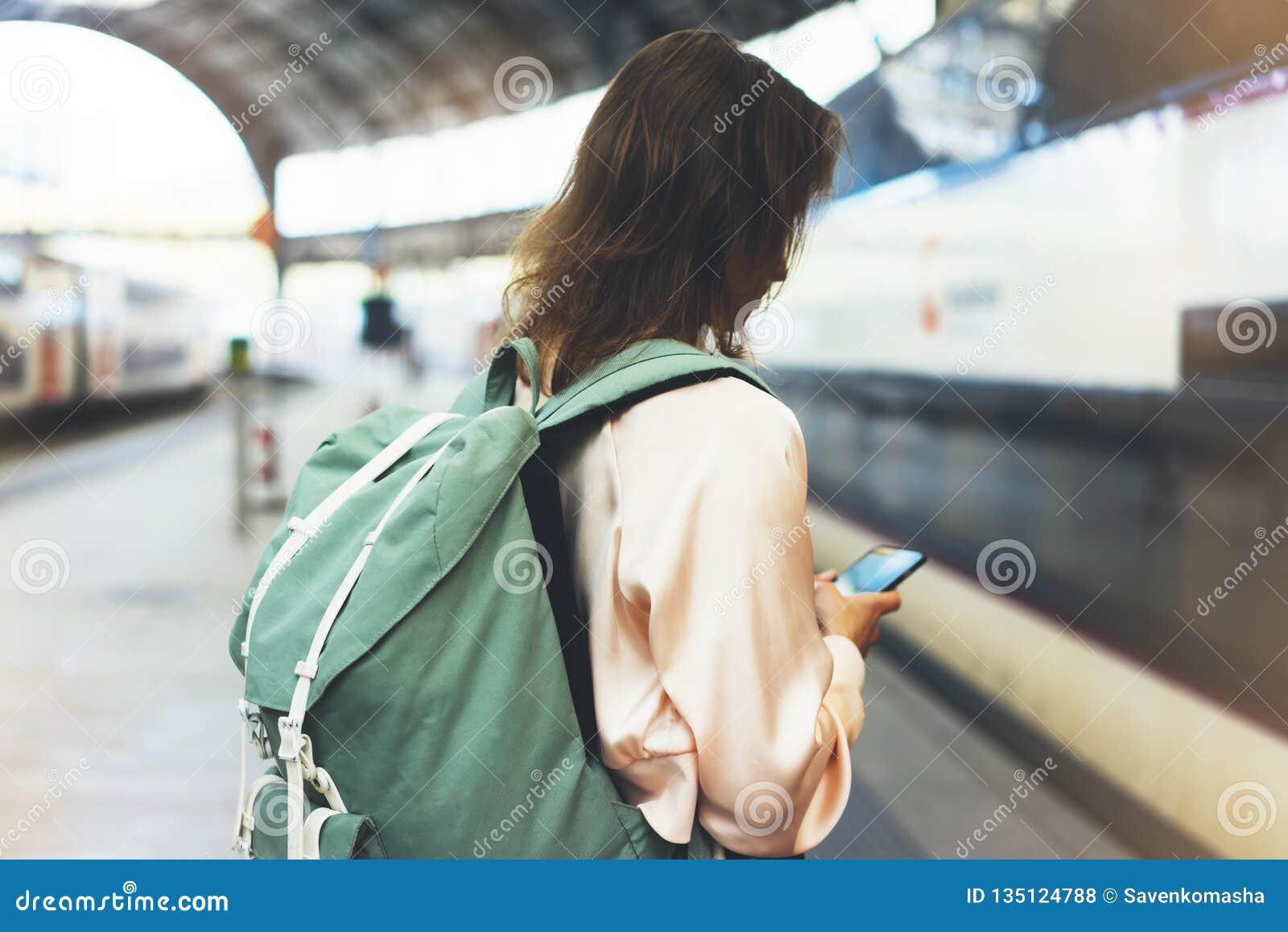 Godere del viaggio Giovane donna graziosa che aspetta sul binario della stazione con lo zaino sul treno elettrico del fondo facen