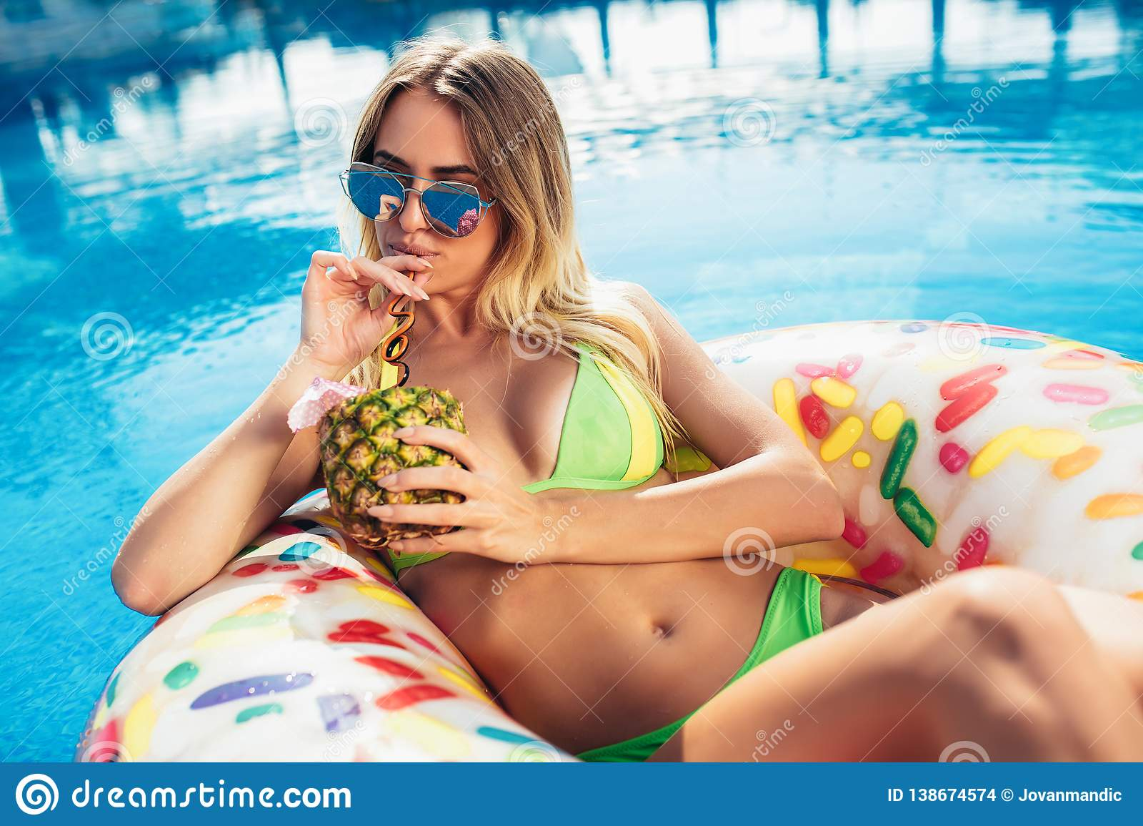 Godere della donna di abbronzatura in bikini sul materasso gonfiabile nella piscina