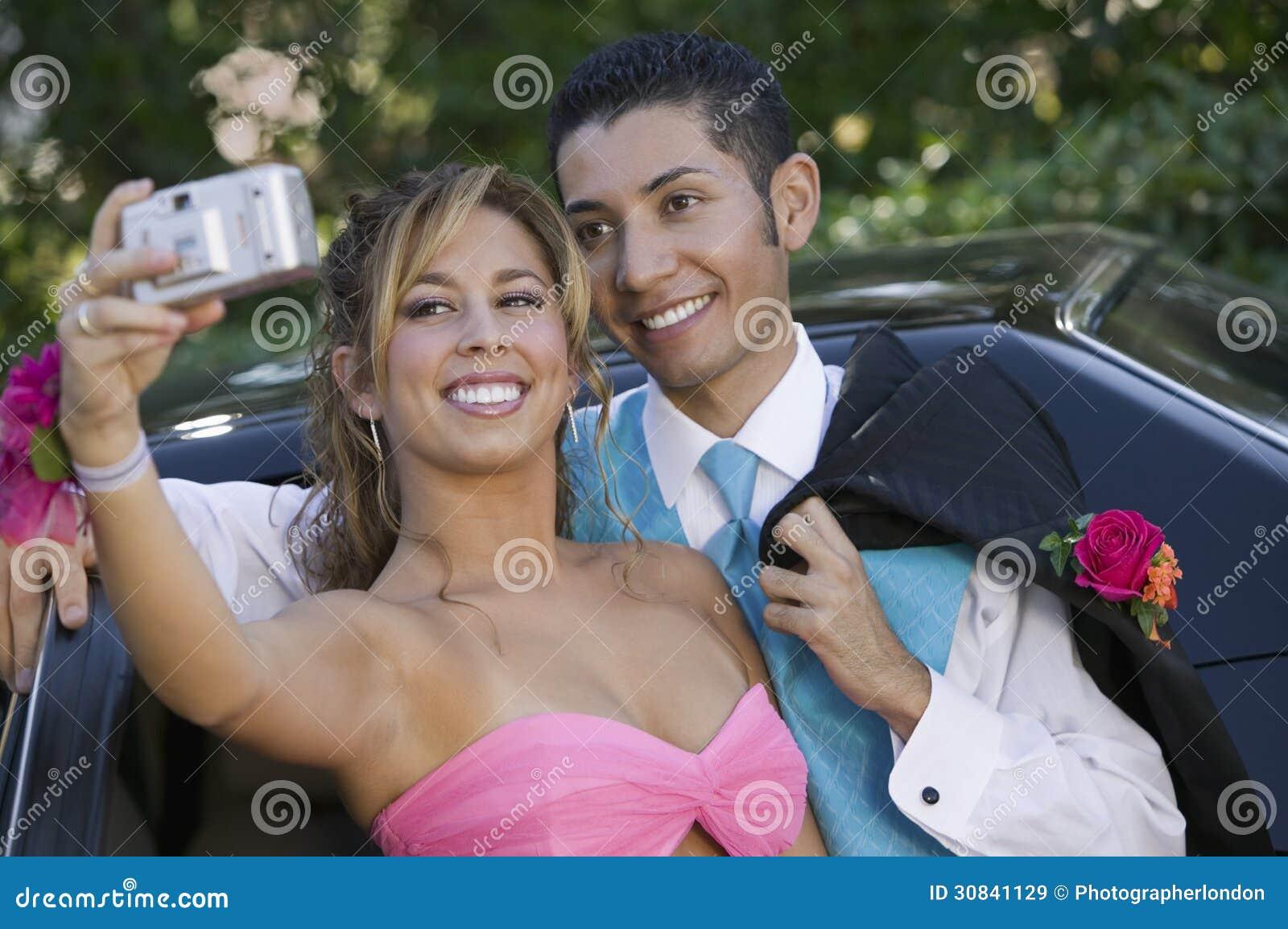 Goed-gekleed tienerpaar die beeld buiten auto nemen