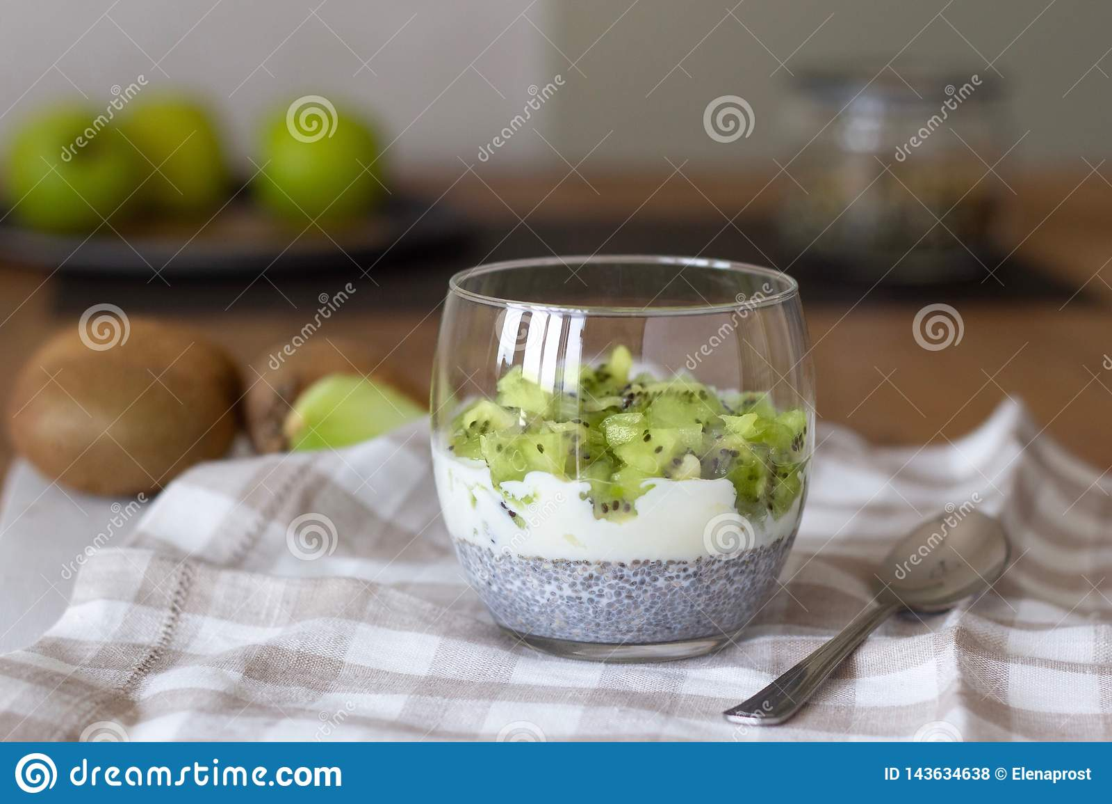 Goed - het zijn en gewichtsverliesconcept, gezond vegetarisch fruitdessert met kiwiyoghurt en de pudding van chiazaden in een gla