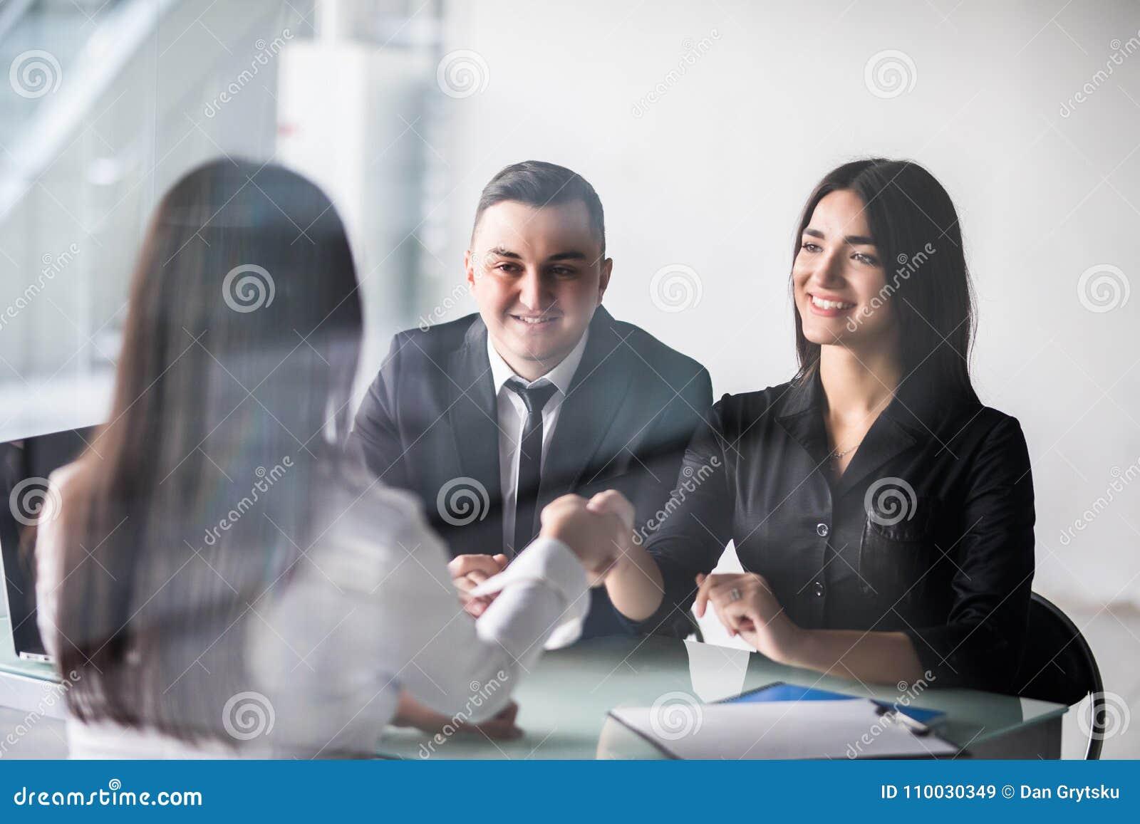 Goede overeenkomst Het vrolijke jonge vrouw plakken op haar echtgenoot terwijl het schudden van hand aan vrouwenzitting voor hem