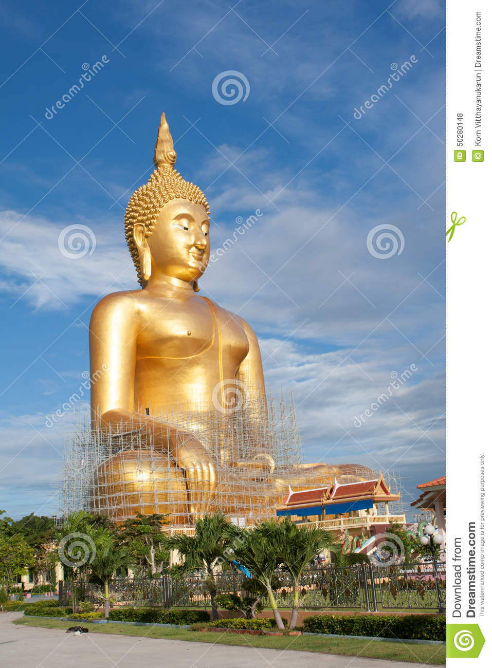 Gold buddha statue under construction in Thai temple with clear sky.WAT MUANG, Ang Thong, THAILAND.