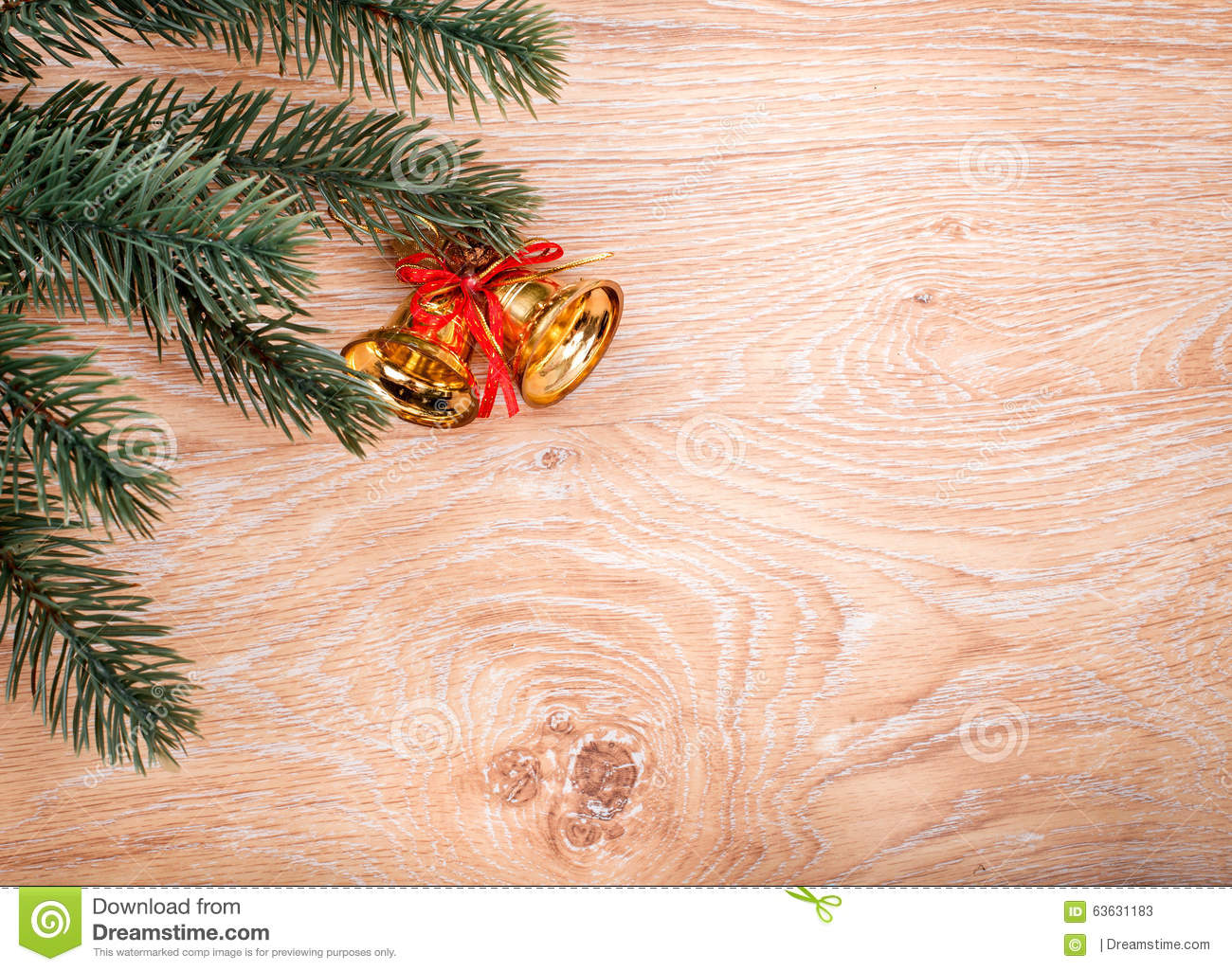 gold christmas bells and fir tree branch on a rustic wooden background