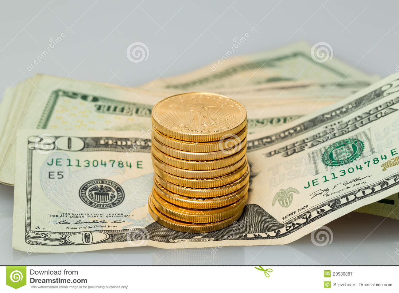stack of 20 dollar bills with gold coins royalty free