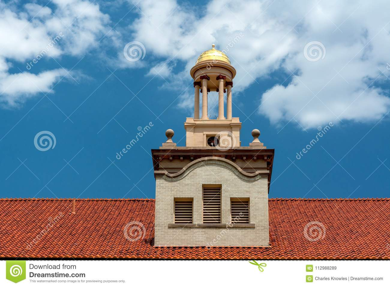Gold dome on the top of a red roofed administration building on