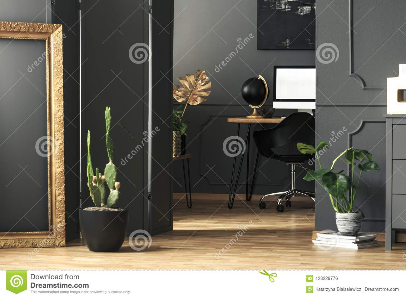 Gold frame next to cactus in grey home office interior with mock
