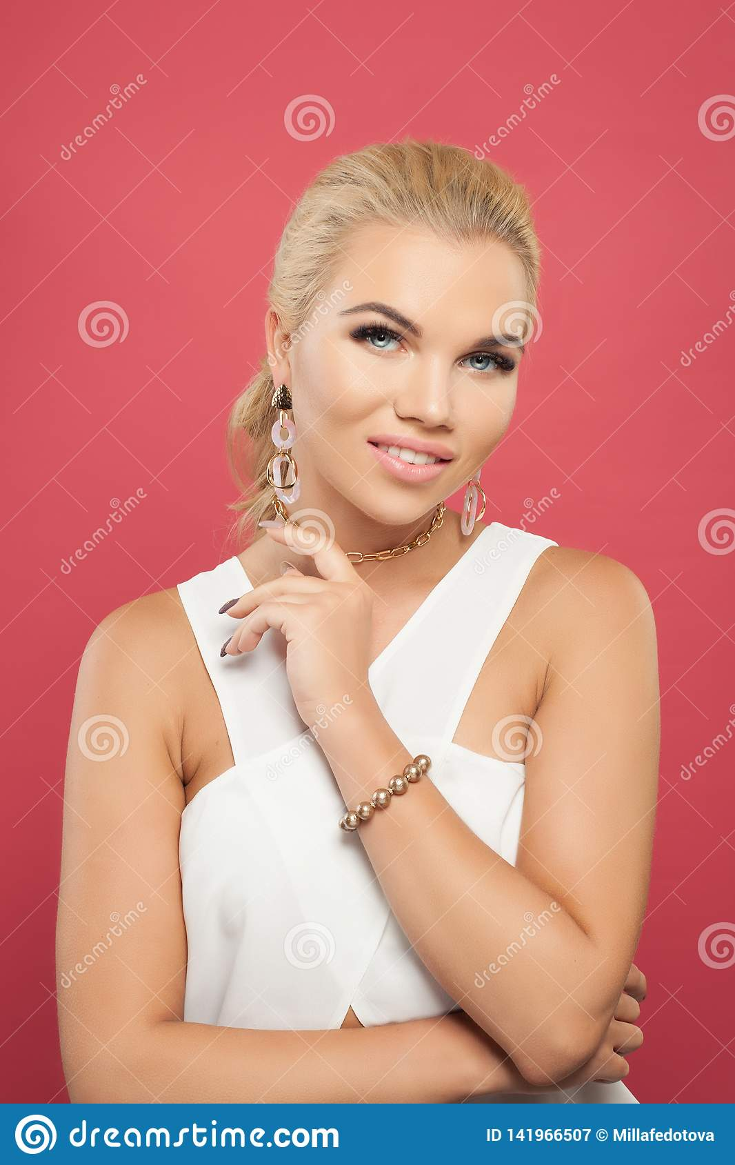Gold jewelry woman portrait. Perfect girl in golden chain necklace, earrings and bracelet against colorful pink wall background