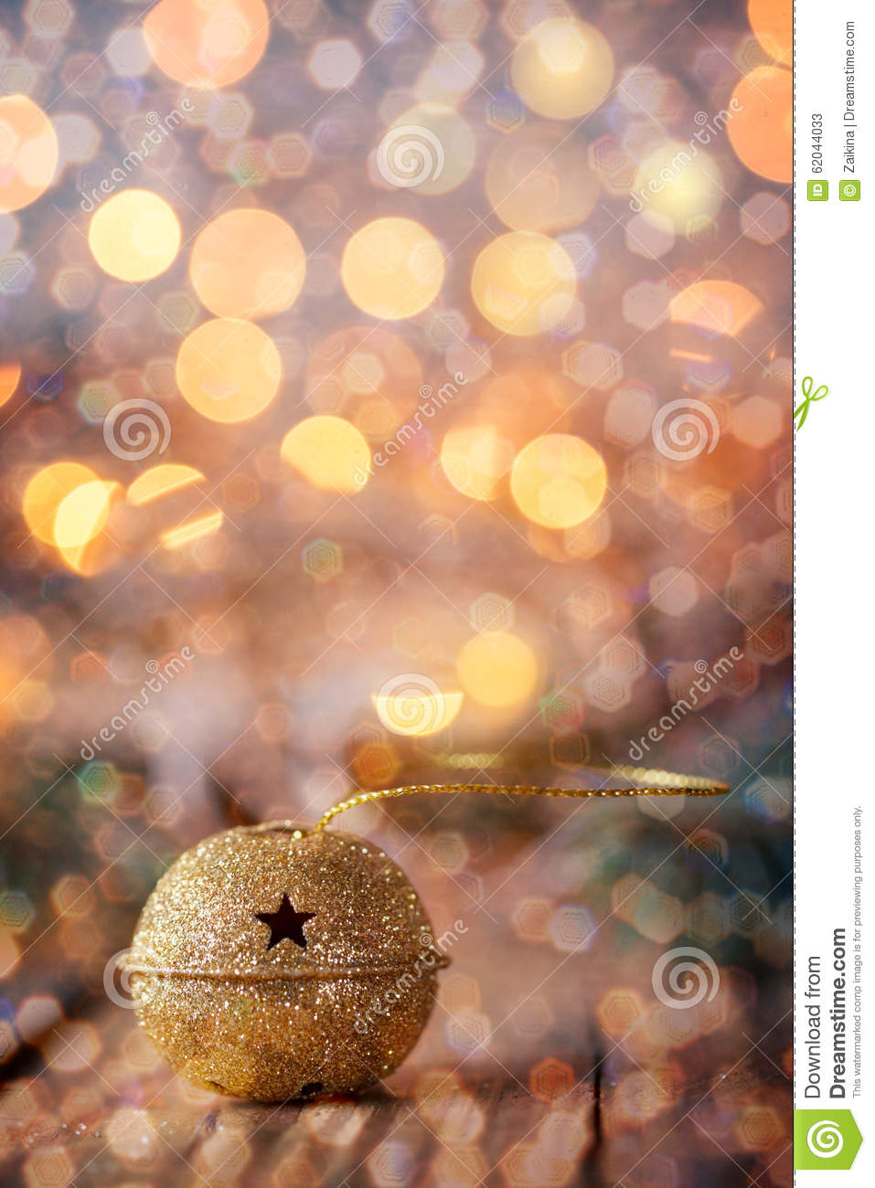 Gold Metal Jingle Bell With Star On Wooden Table Boke