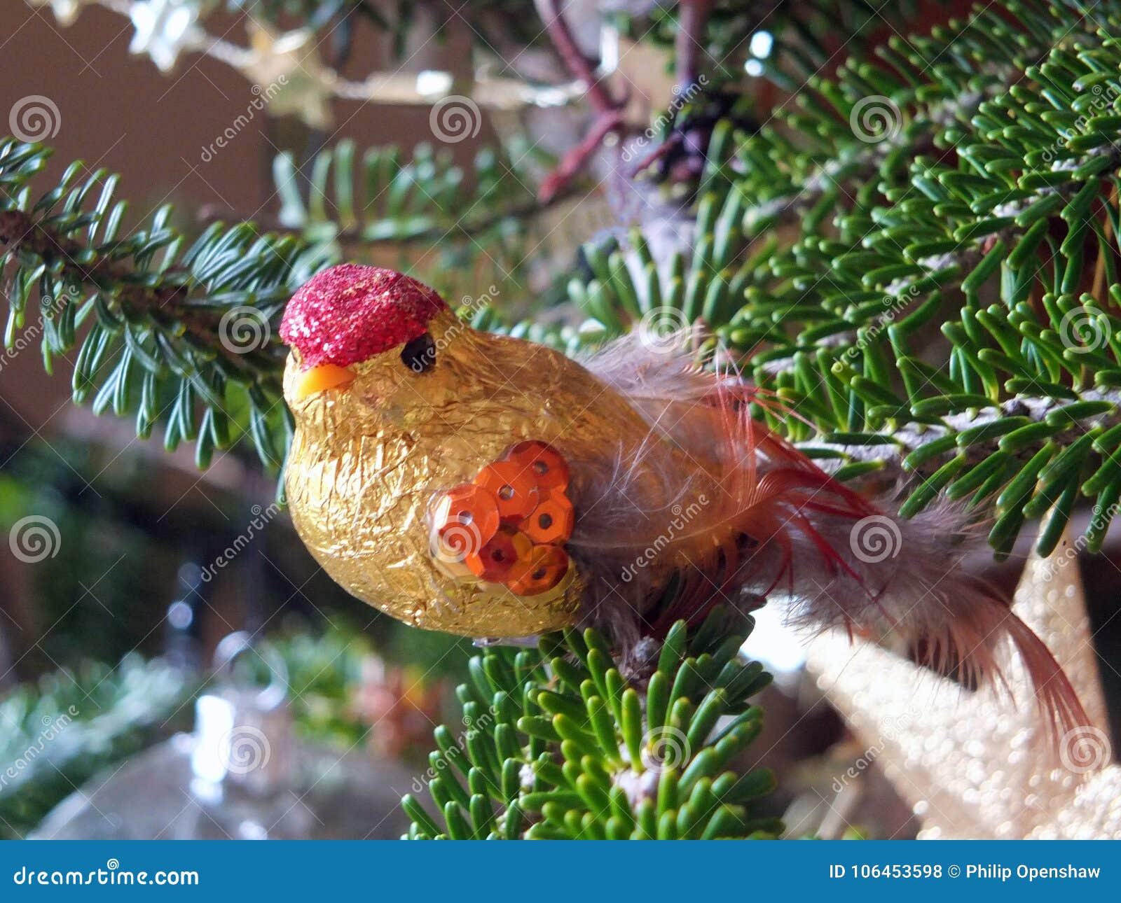 gold shiny bird christmas tree decoration on a pine branch