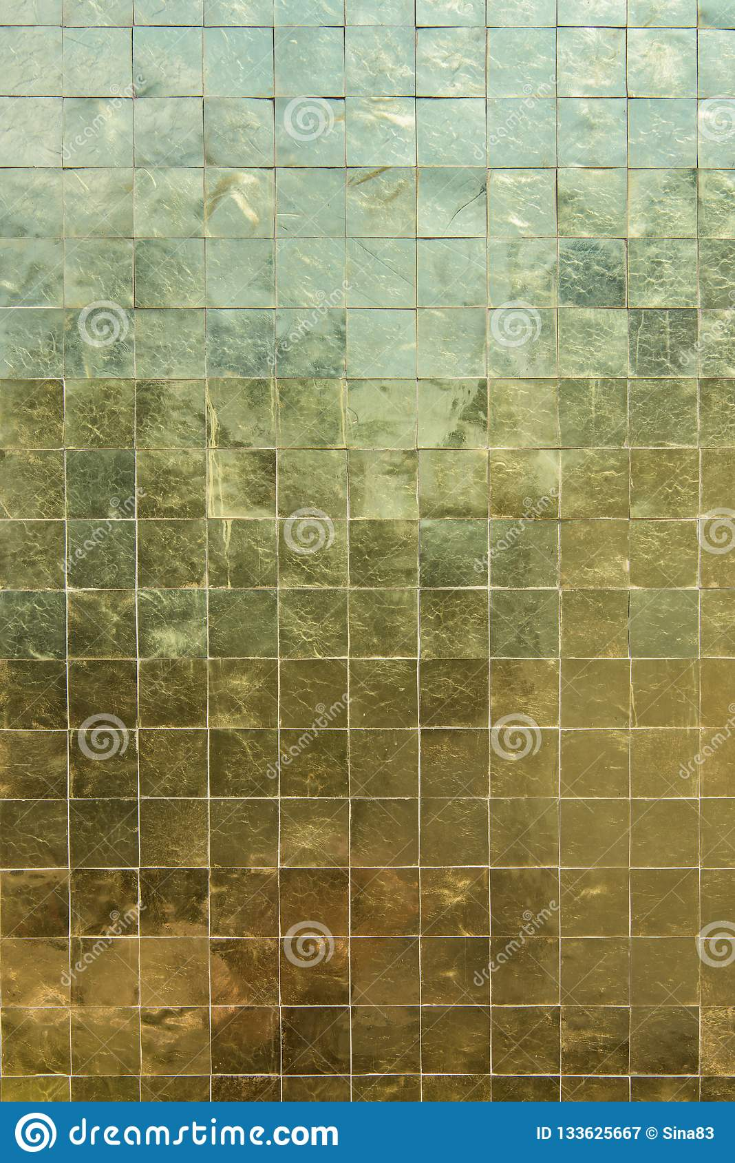 Gold surface small mosaic tiles closeup shining yellow background