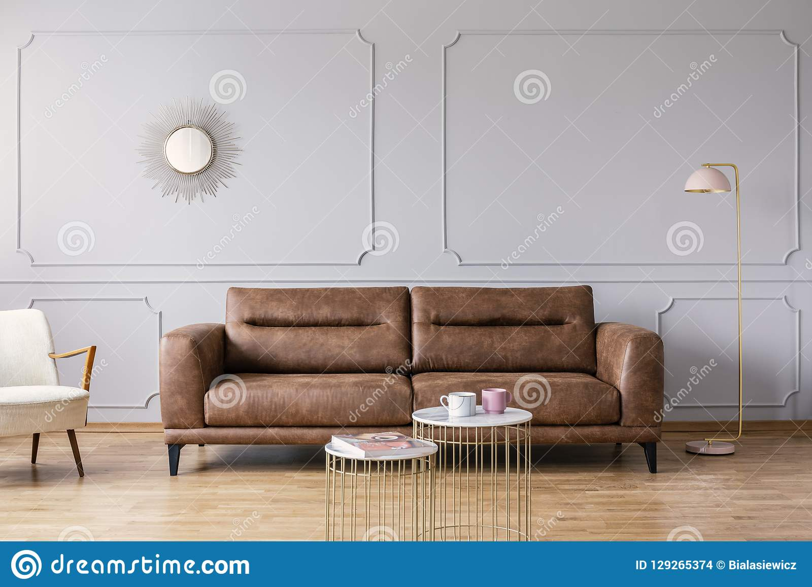 Gold Tables In Front Of Leather Sofa In Grey Elegant Living