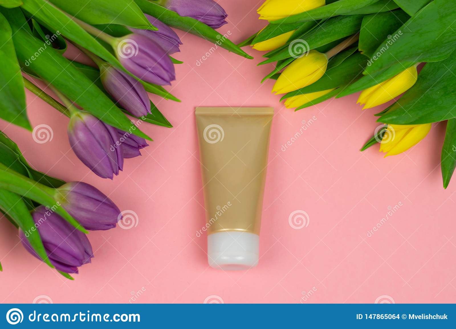 Empty tube of cream on a pink background with flowers