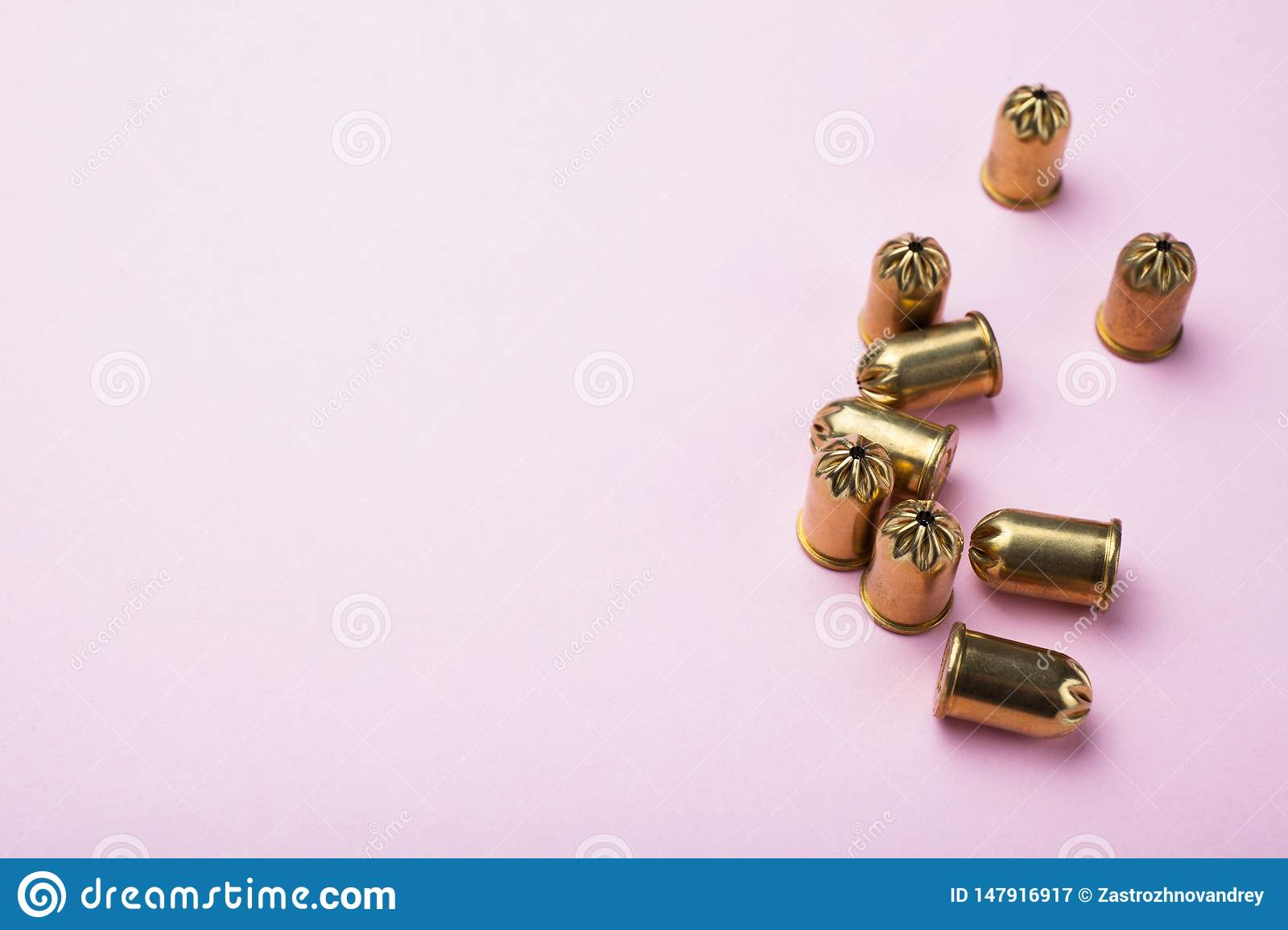 Gold vintage bullets on a pink background, blank space for text