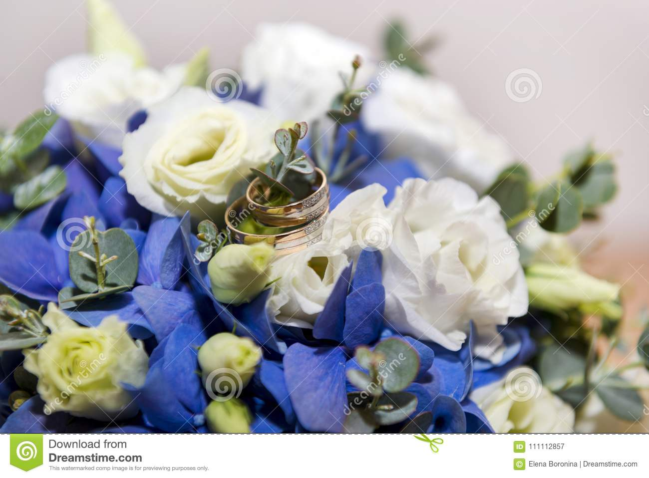 Gold Wedding Rings On A Bouquet Of White And Blue Flowers Stock