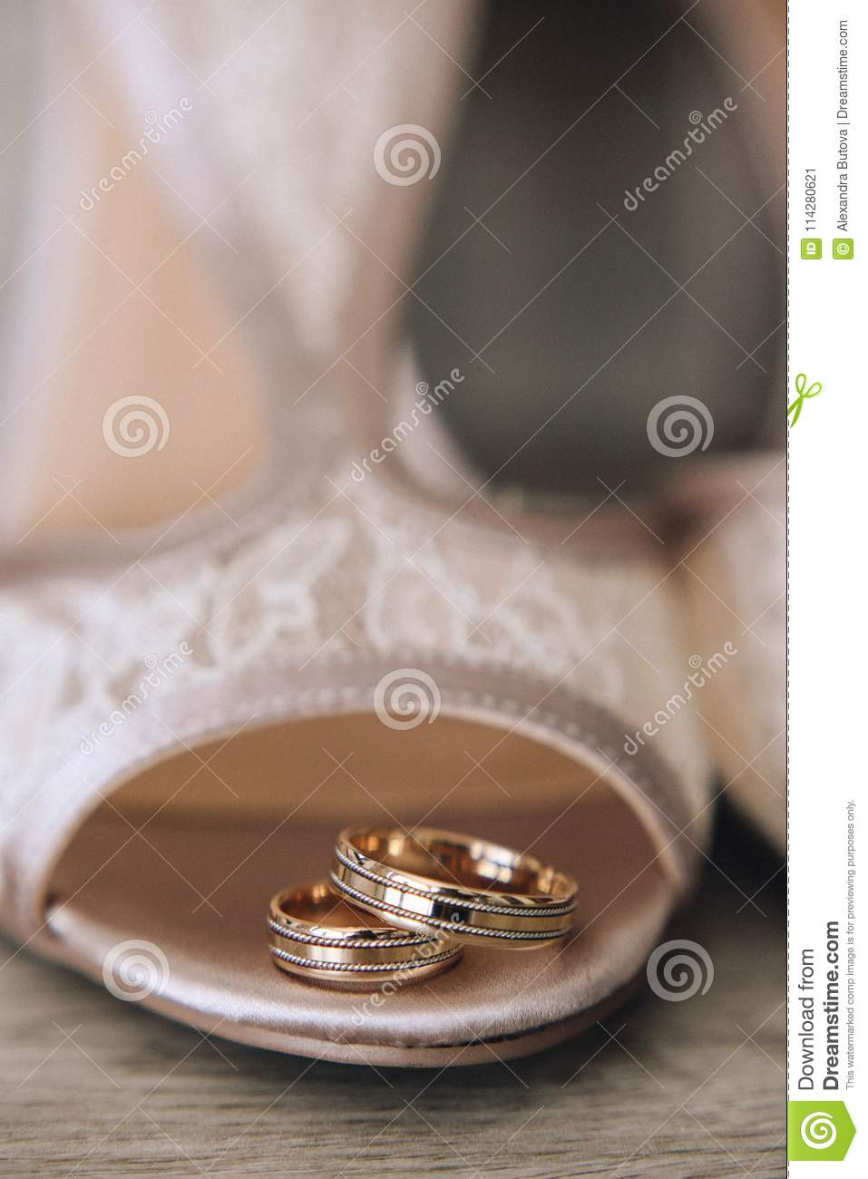 Gold wedding rings with a design are on the bride`s shoes with a lace. Close up