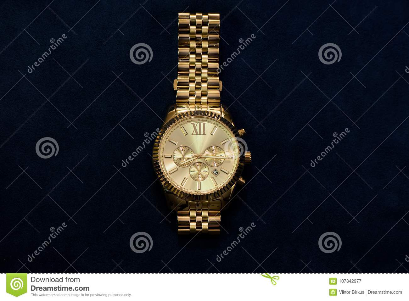 Gold wristwatch with a yellow metal bracelet on a dark blue back