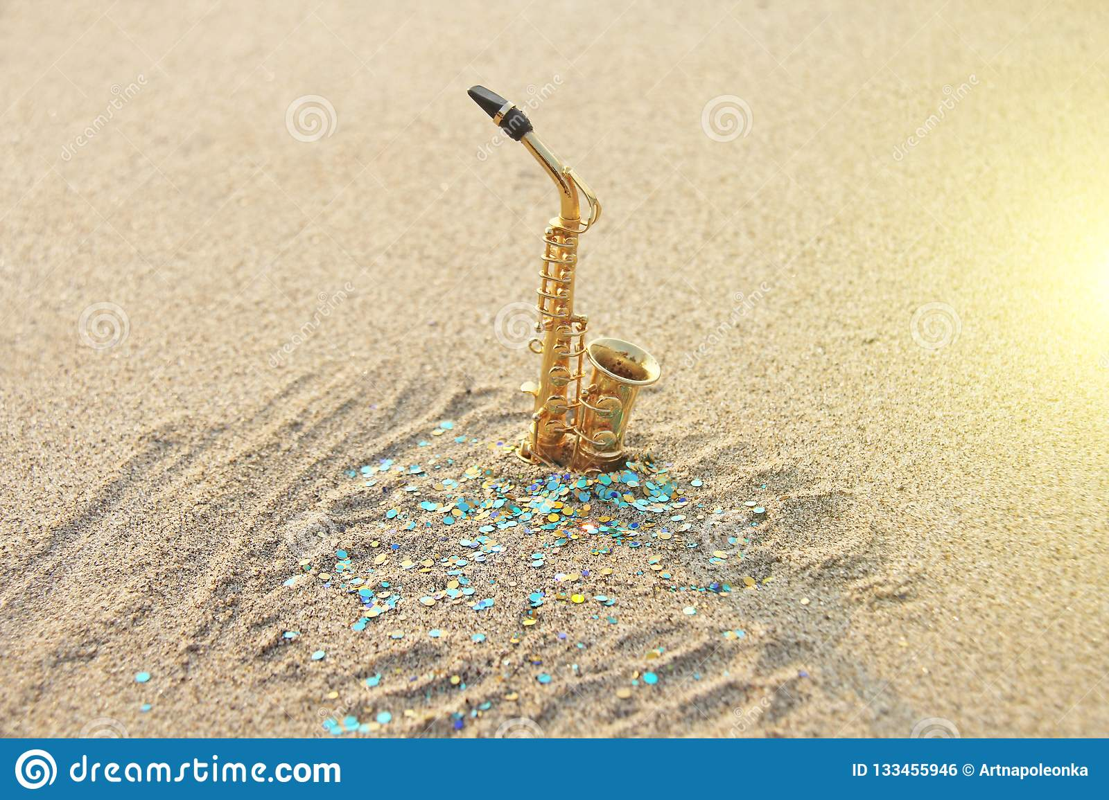 The golden alto saxophone stands on the sand against the background of blue shimmers. Romantic musical background. Musical