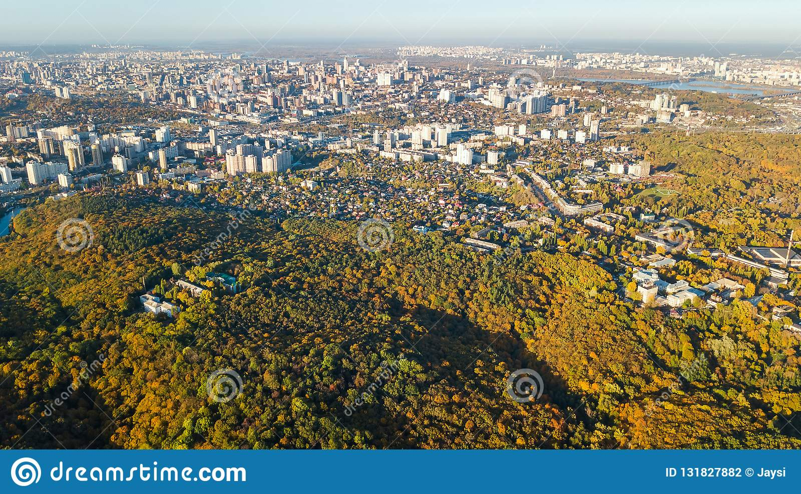 Golden autumn Kyiv cityscape, aerial drone view of city skyline and forest with yellow trees and beautiful landscape from above