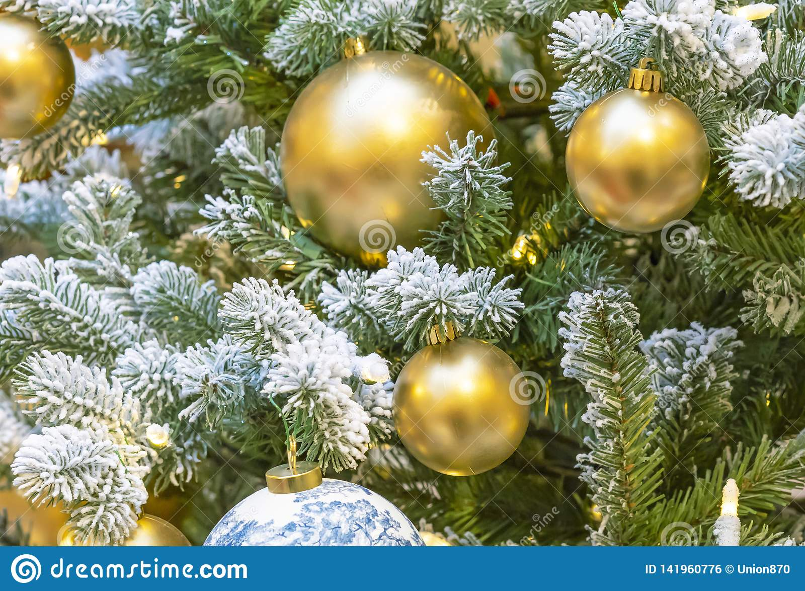 Golden balls and a garland on a snowy Christmas tree