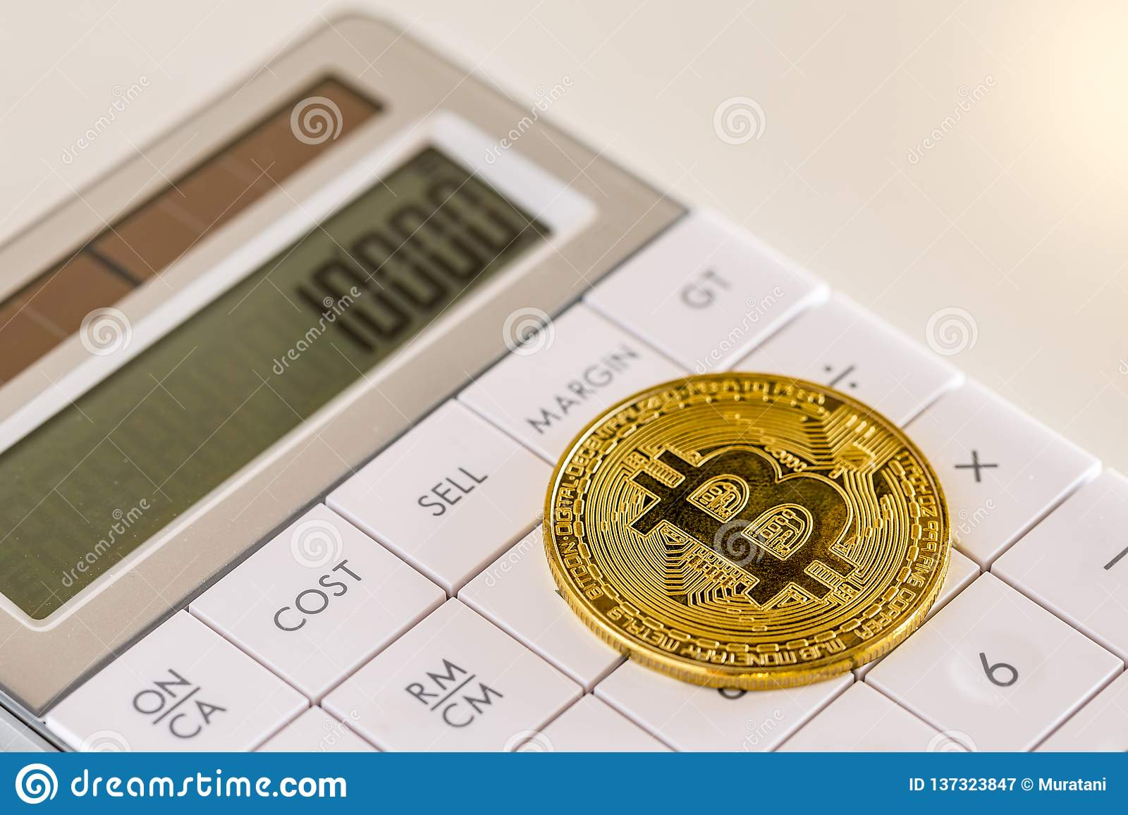 Golden Bitcoin On White Calculator Close-up Image Stock
