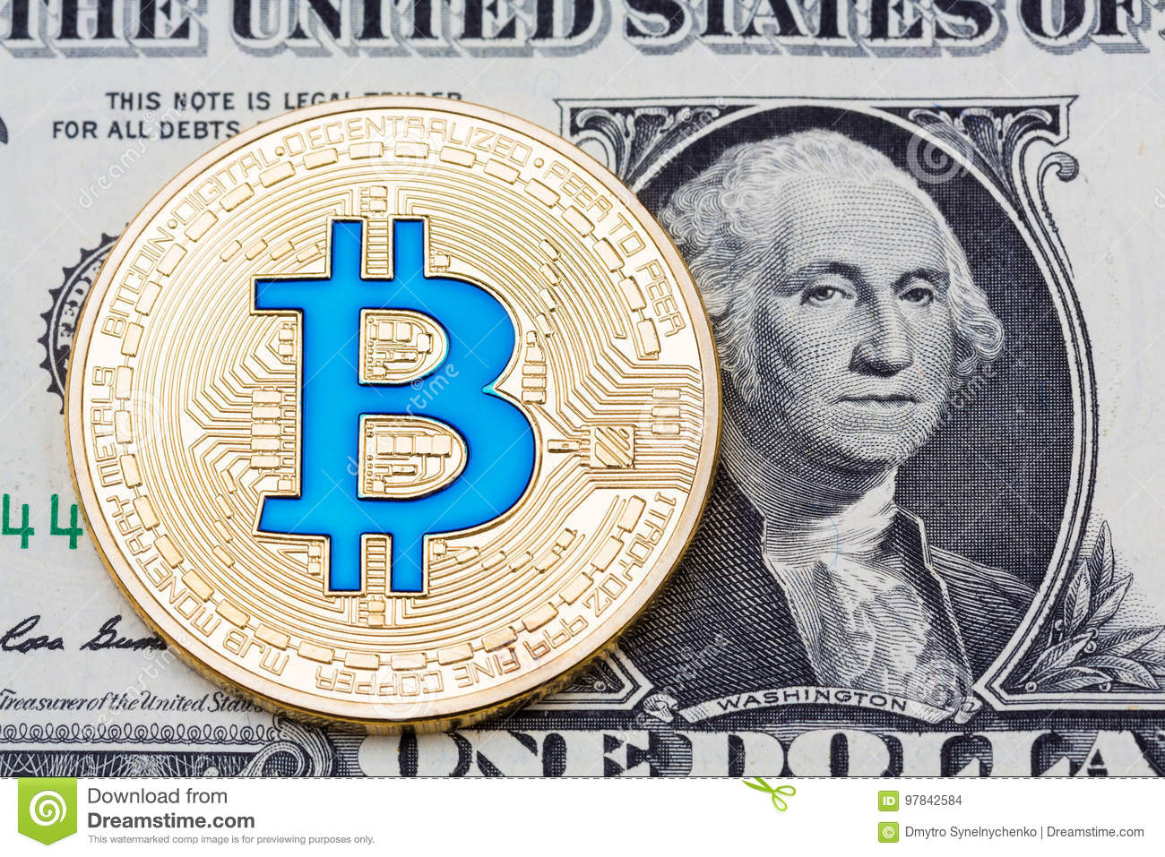 Golden blue bitcoin coin on us dollars close up.