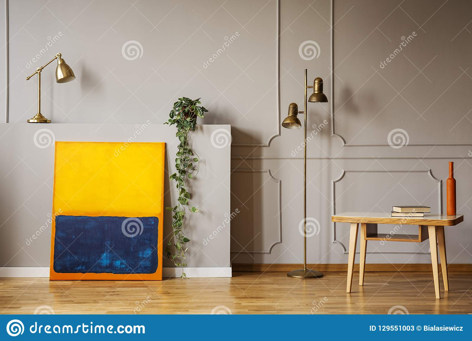 Golden Brass Floor Lamp An Abstract Painting And A Wooden Desk In A Gray Living Room Interior Place For Armchair Real Photo Stock Image Image Of Interior Armchair 129551003