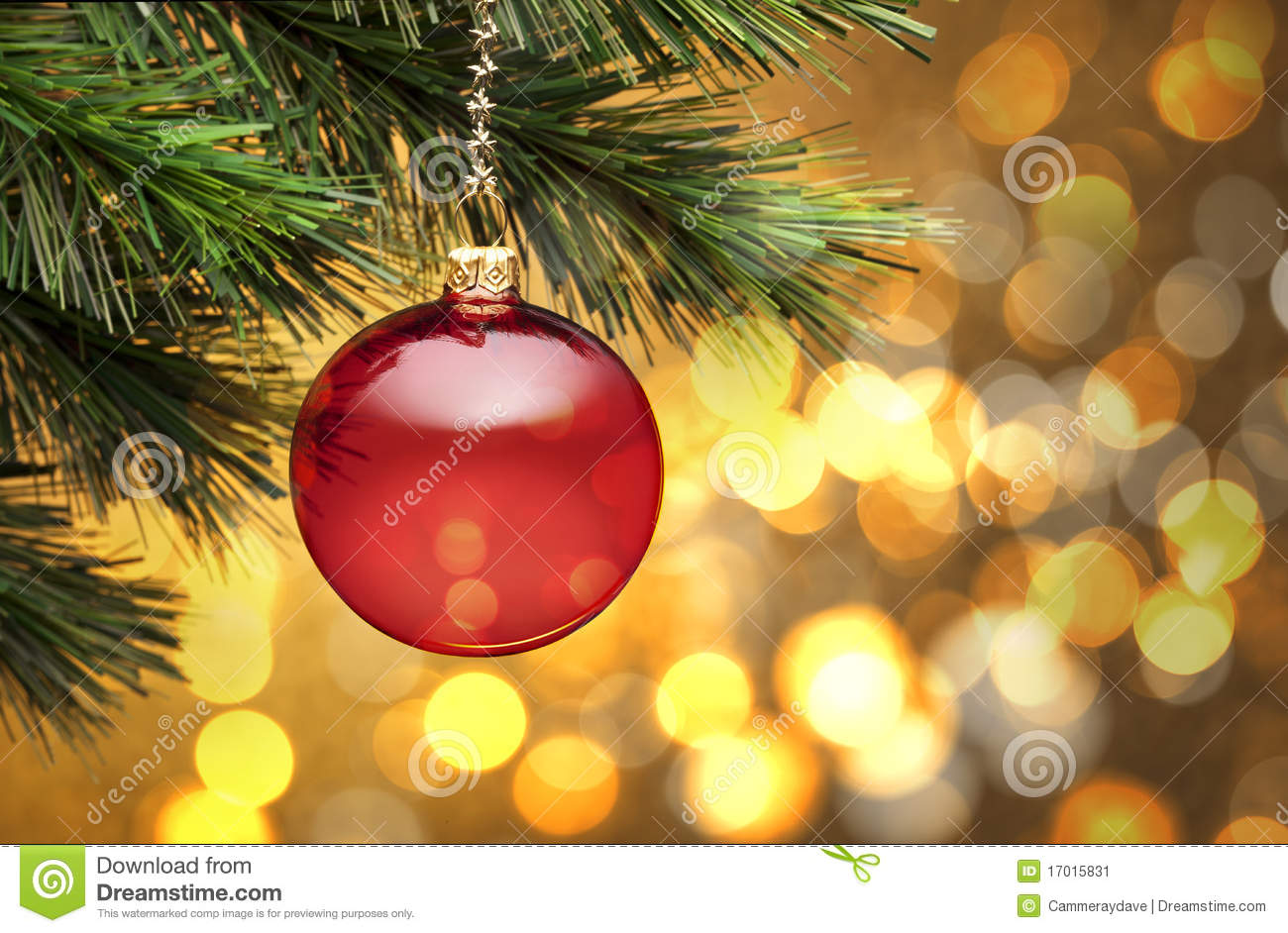 red christmas ornament hanging from a tree with golden lighting with ...
