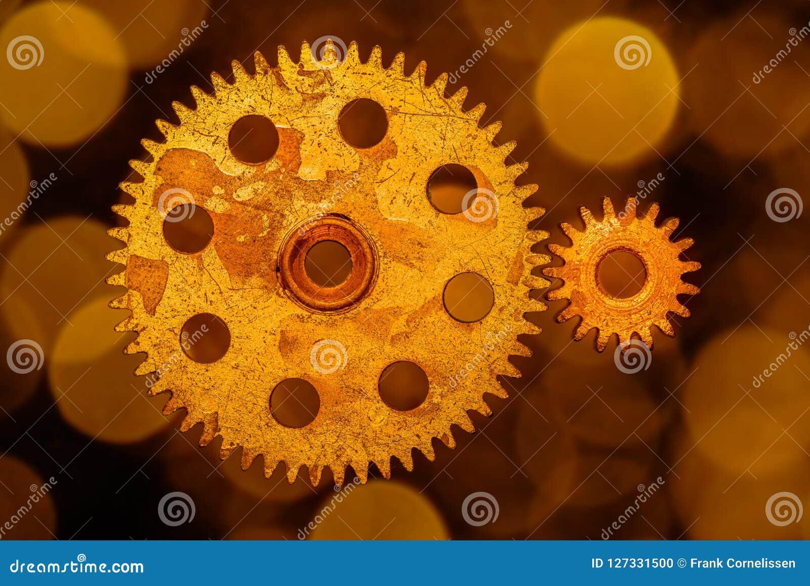 Golden cogwheels on a background of gold circled bokeh.