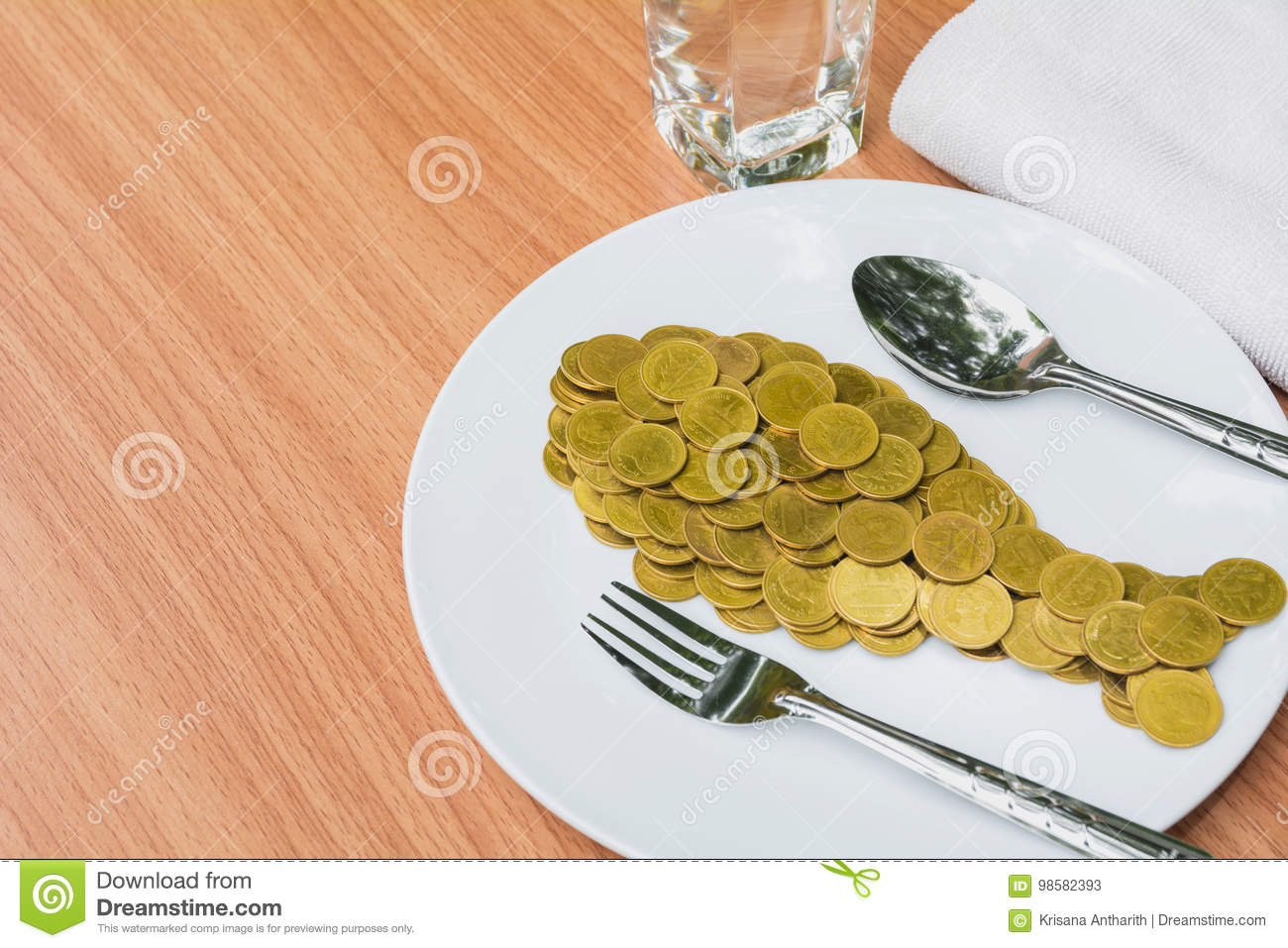 Golden coins shape fish with spoon and fork in white plate