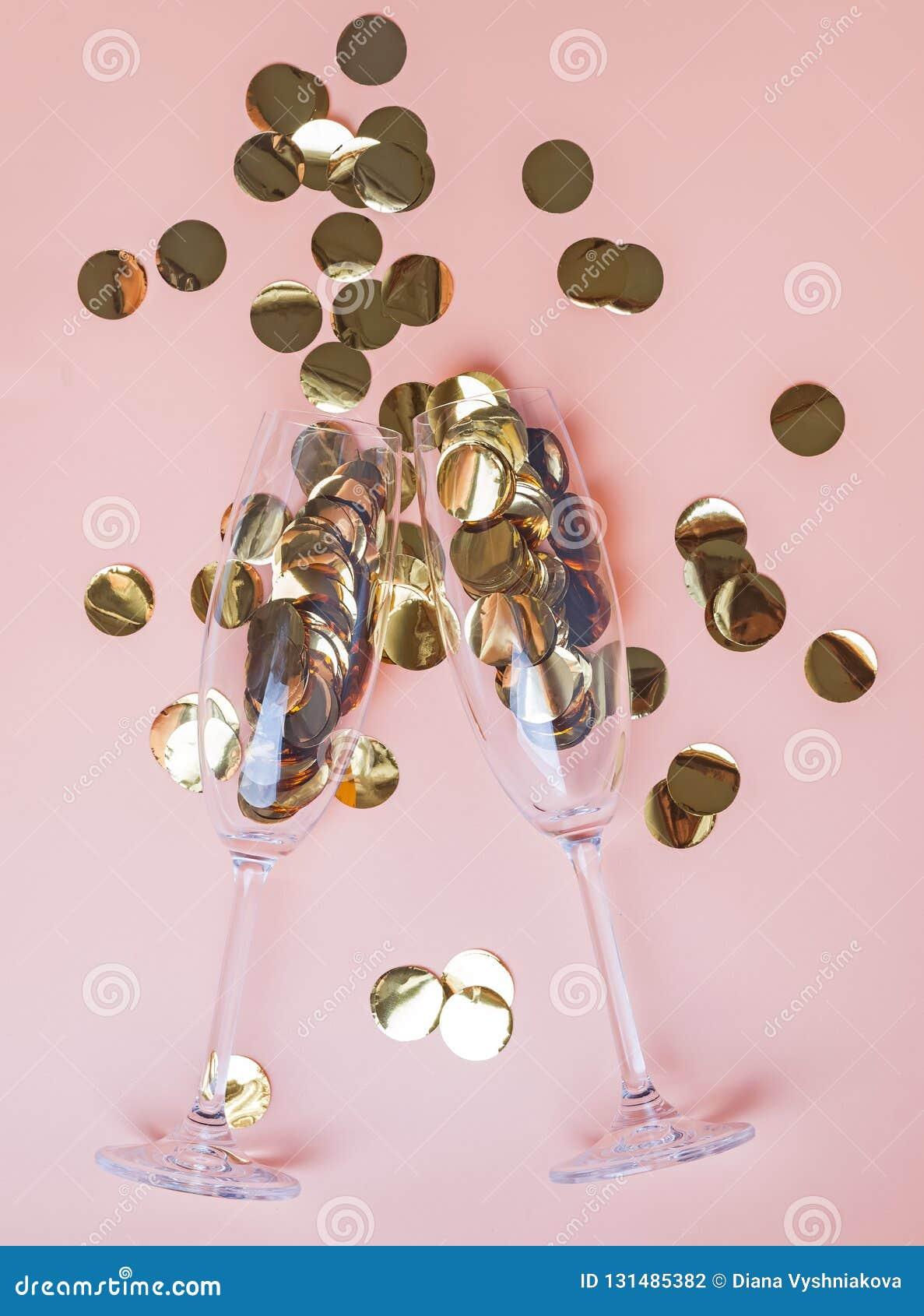 Golden confetti in champagne glasses on the peach color background