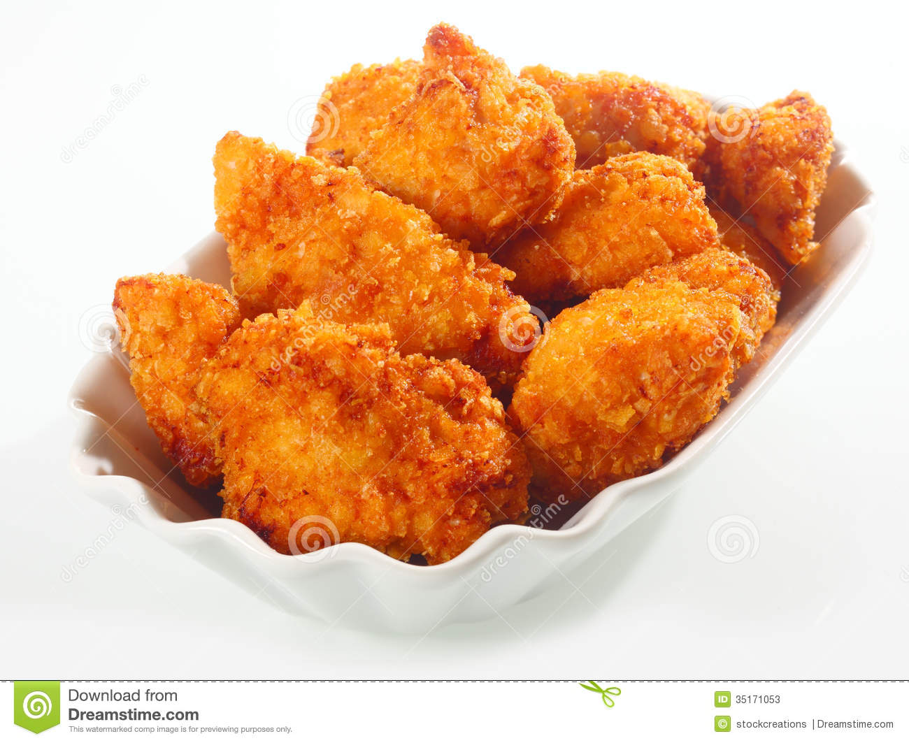 Golden crisp fried crumbed chicken nuggets served in a fluted dish as ...