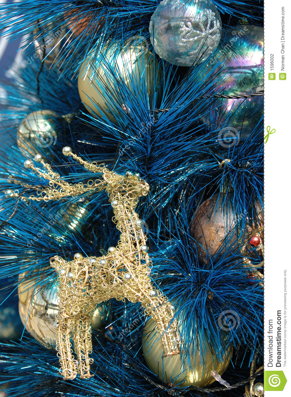 Blue and gold christmas tree decorations - Golden Deer Ornament On Blue Christmas Tree Stock Photography