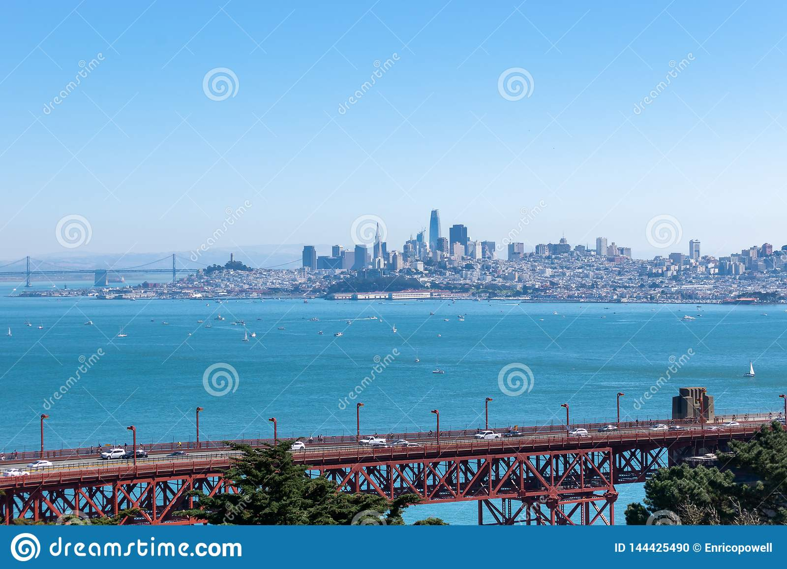 Golden gate bridge i Kalifornien med horisont av den i stadens centrum San Francisco och Oakland fjärdbron
