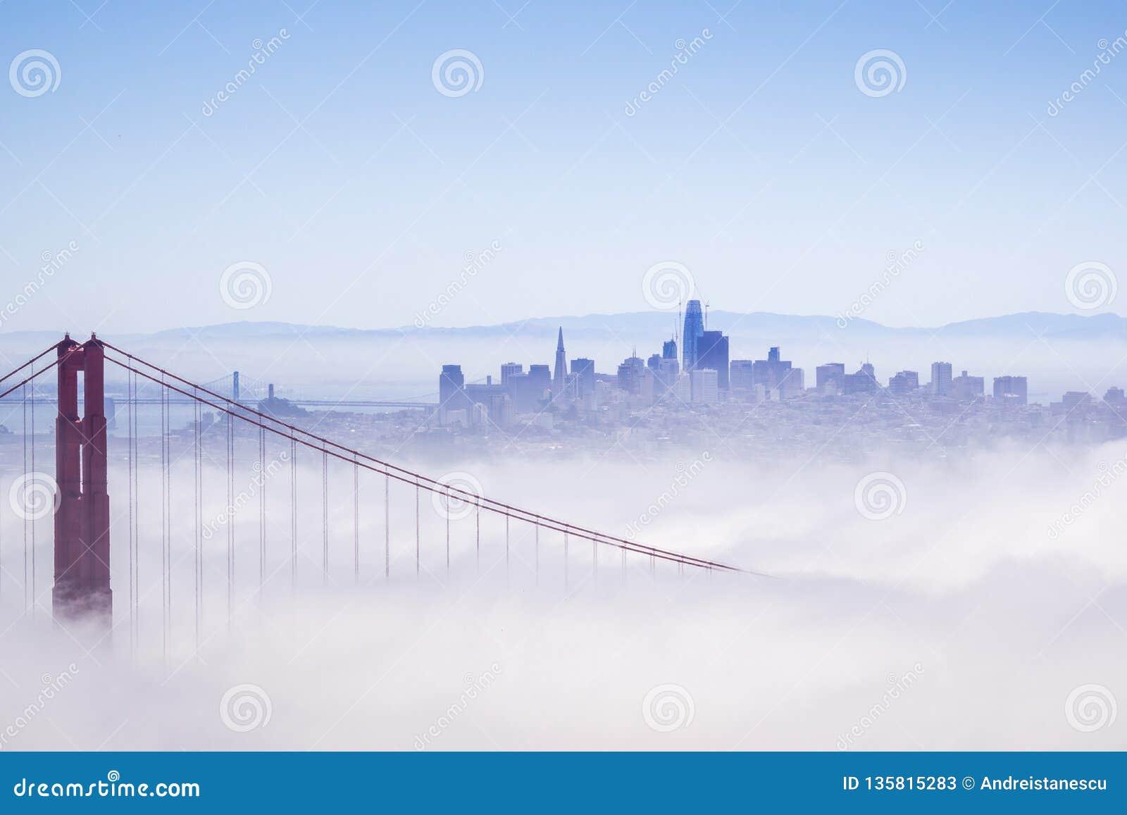 Golden Gate e o San Francisco Bay coberto pela névoa, a skyline financeira do distrito no fundo, como visto do Marín