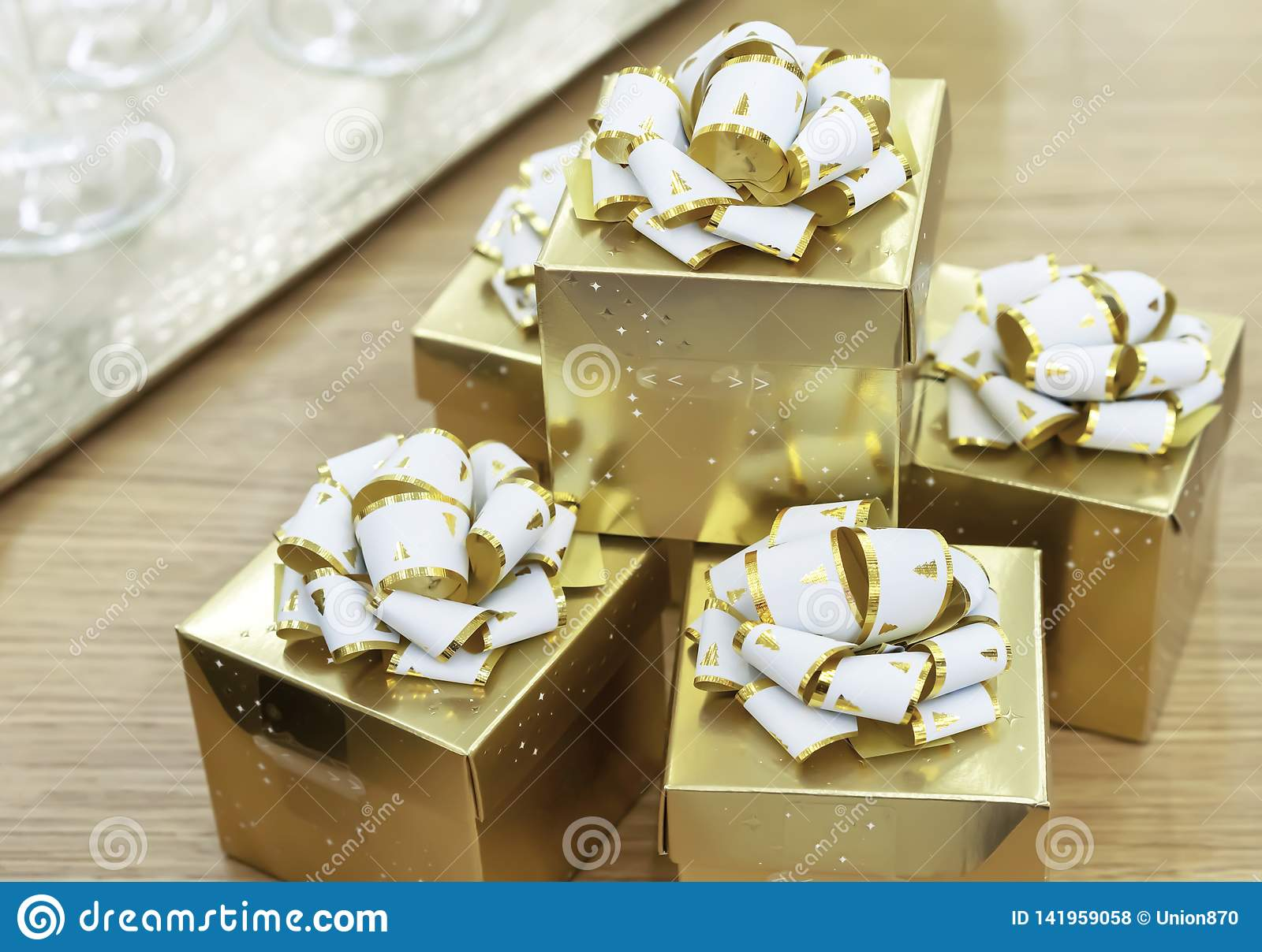 Golden gift boxes with white bows on a wooden table