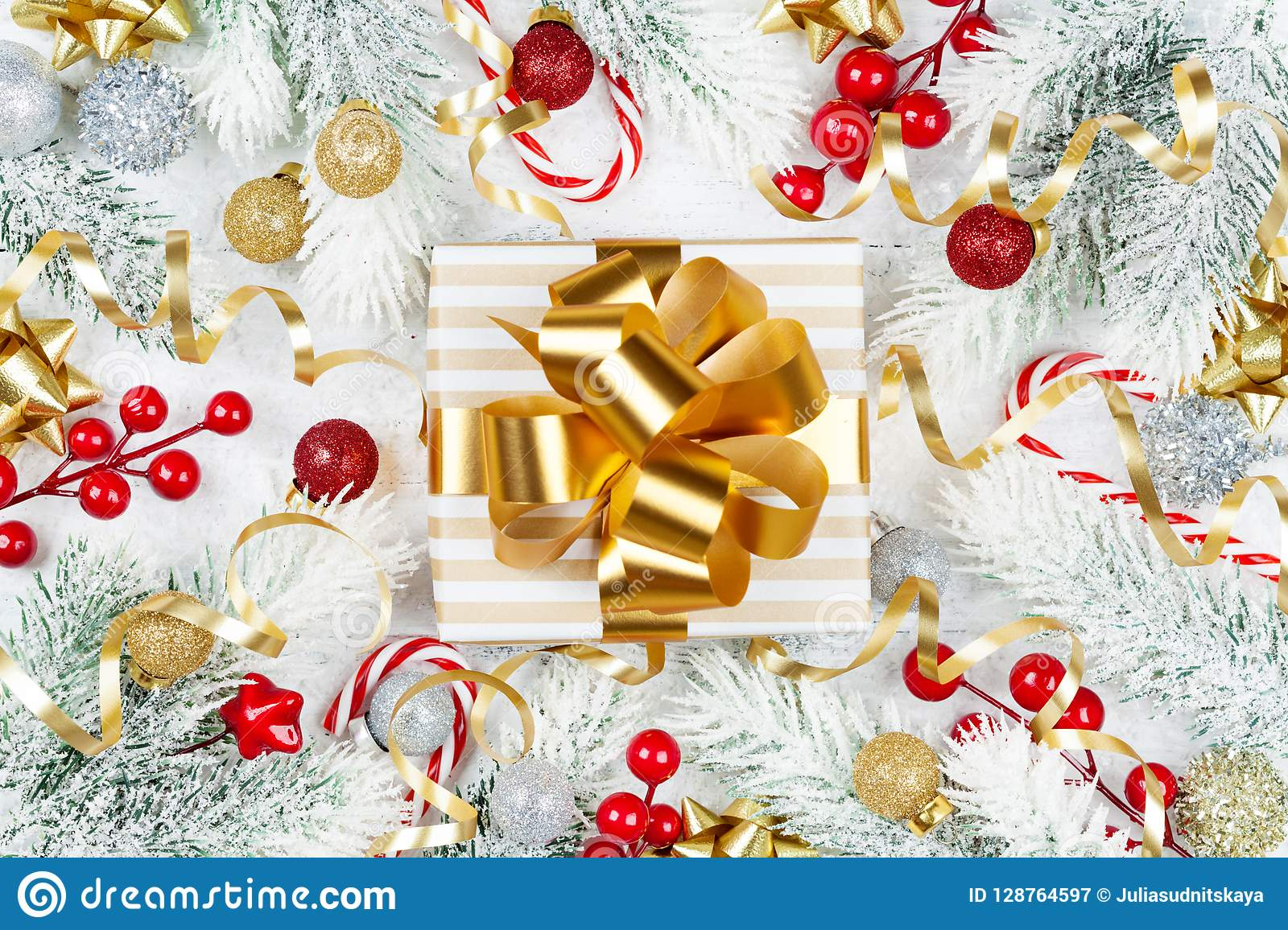 Golden gift or present box, snowy fir tree and christmas decorations on white wooden table top view. Flat lay.