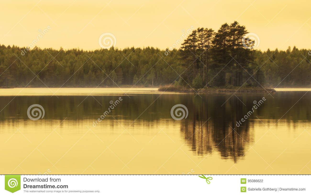 Golden hour beautiful reflection of small island in lake.