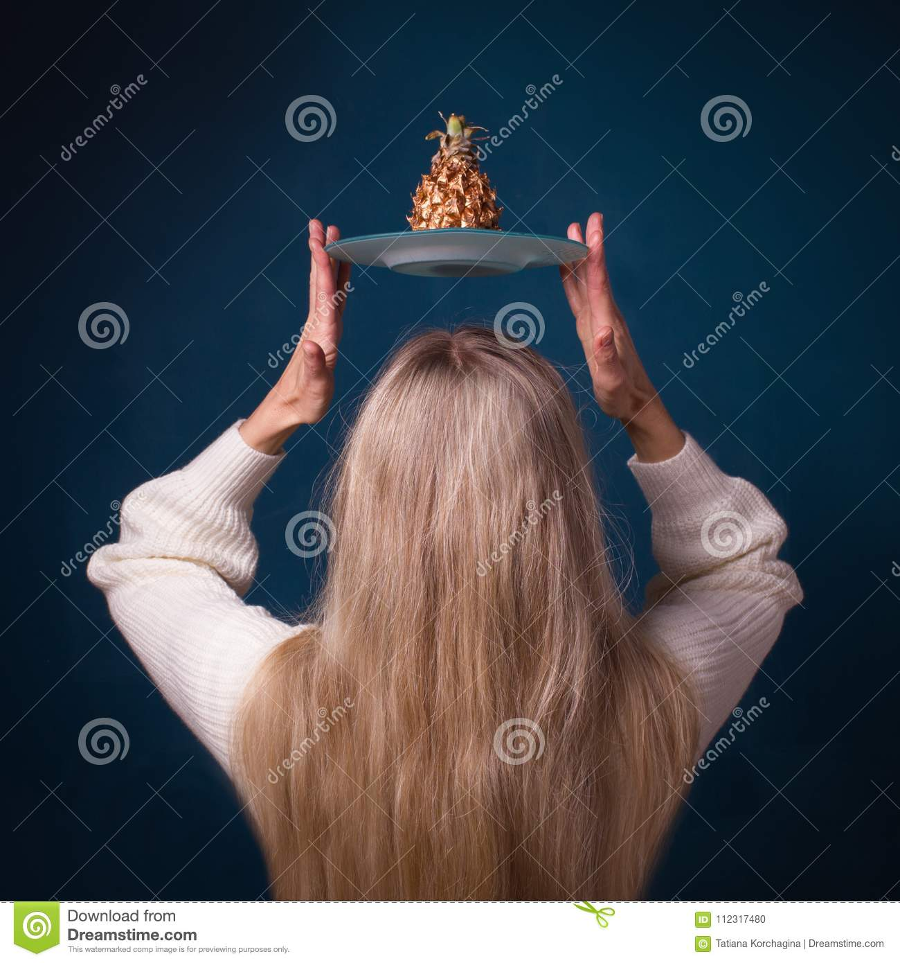 Golden pineapple fruit above the head of woman