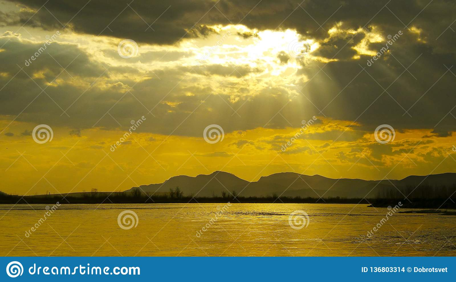 The golden ray of the sun from behind a dark cloud illuminates the evening lake