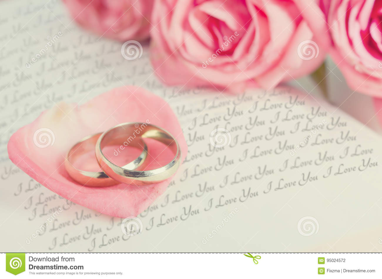 Golden Rings On Pink Rose Petal On Opened Book Stock Photo - Image ...