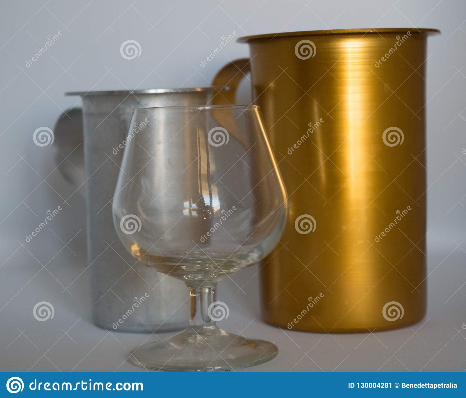 Golden and silvery pitcher with cognac glass empty on white background