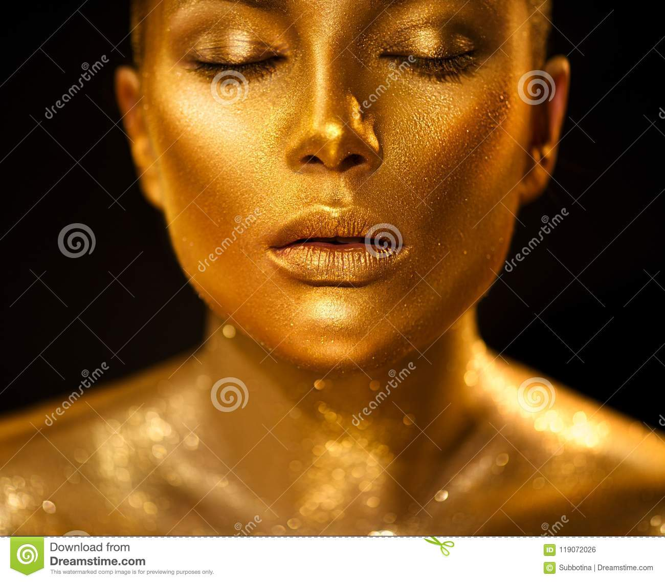 Golden skin woman face. Fashion art portrait closeup. Model girl with holiday golden glamour shiny professional makeup