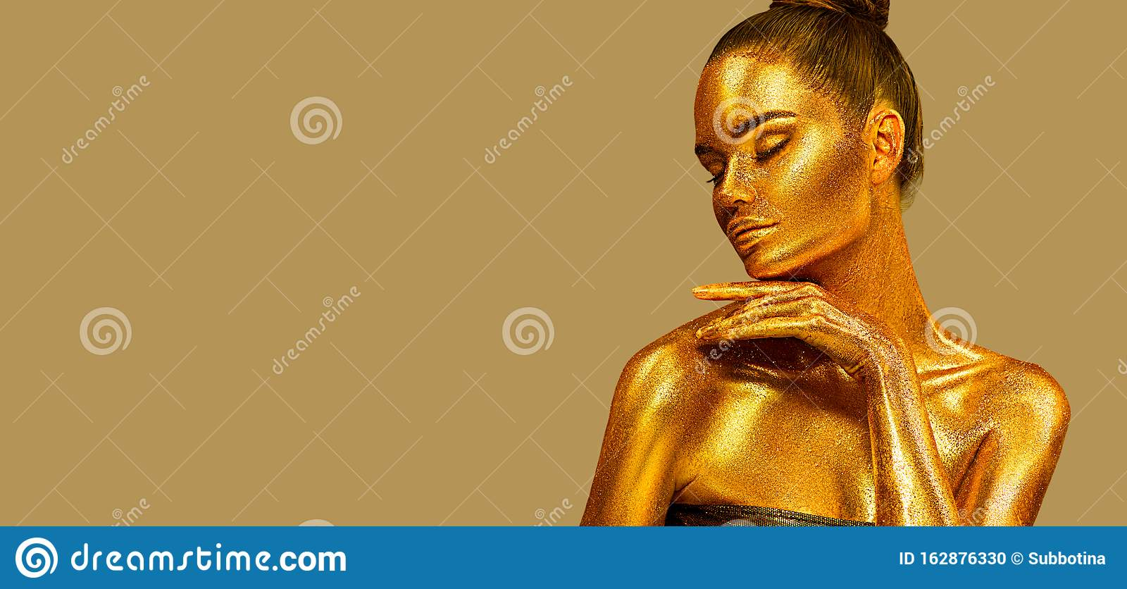 Golden sparkles skin, Woman face portrait closeup. Model girl with holiday golden Glamour shiny professional make up